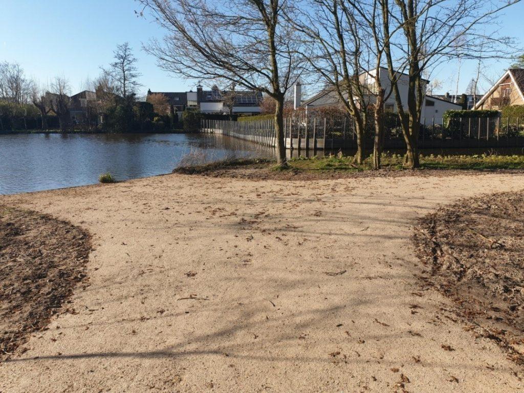 Foto van een wandelpad in een parkje bij het water