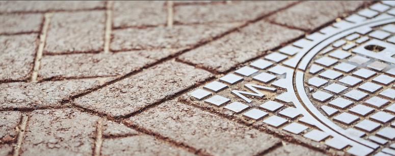 Op de foto ziet u asfalt met streetprint en een deel van een putdeksel.